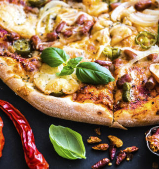 tasty pizza on a black background with spices and herbs